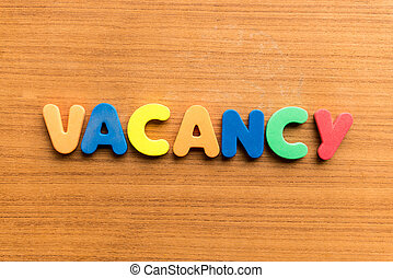 vacancy colorful word on the wooden background colorful word...