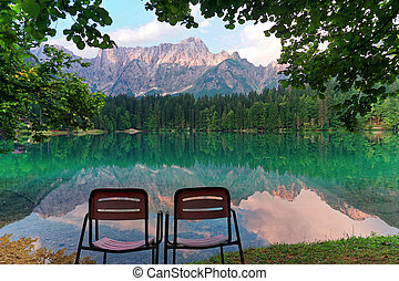 Vacant Chairs admiring fusine lakes reflection landscape...