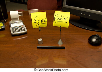 Gone Fishin\' - Vacant desk with \'Gone Fishin\' on Post-It...