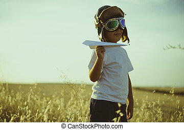 Vacation, Boy playing to be airplane pilot, funny guy with aviator cap and glasses, carries in his hand a plane made of paper