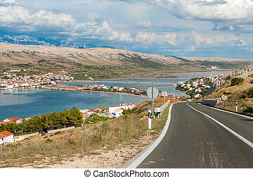 Driving through Pag island with the view of Pag town, Adriatic coast and Velebit mountains, Croatia