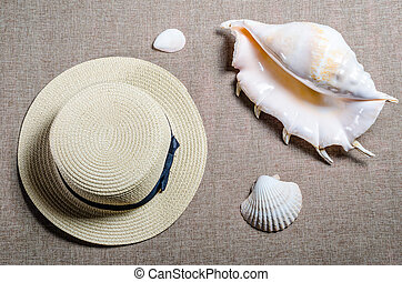 vacation flat view with straw hat and big ocean sea shells on the mat