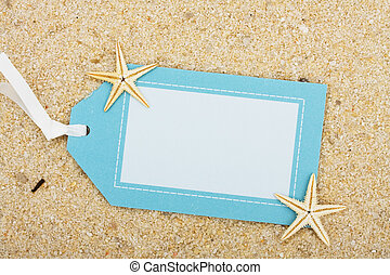 A blank gift tag sitting on a sand background, vacation gift tag