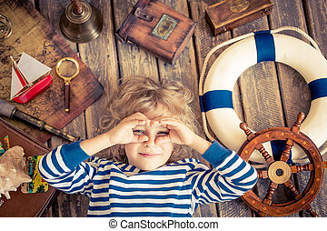 Happy kid playing with nautical things. Child having fun at home. Travel and adventure concept. Unusual high angle view portrait