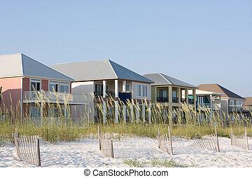 Vacation rental homes sit among the sea oats along the coastline.