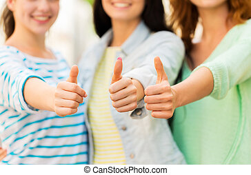 close up of happy young women showing thumbs