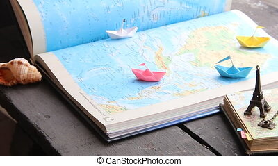 Vacation or Holiday concept. Paper boats on the map and the Eiffel Tower.