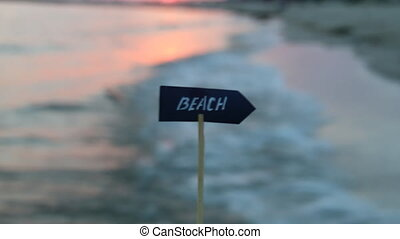 Vacation or holidays idea - beach sign and sunset