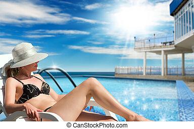 Vacation - The sunbathing woman near a swimming pool