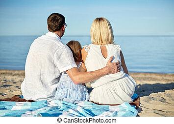happy family hugging on summer beach