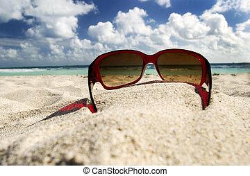 Sunglasses on the beach against the sky and ocean