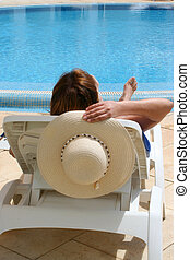 vacation time - woman relaxes by the pool