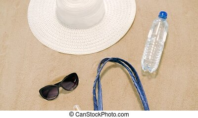 beach bag, sunscreen, sunglasses and hat on sand - vacation,...