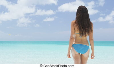 Vacation travel bikini woman on Caribbean beach. Lady with slim sexy body standing from behind on tropical white sand beach in Caribbean looking at perfect turquoise ocean. Luxury destination. SLOW MO