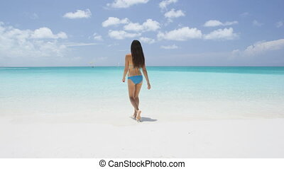 Vacation travel bikini woman walking on Caribbean beach into water. Lady with slim sexy body on tropical white sand beach in going swimming in perfect turquoise ocean. Luxury destination.