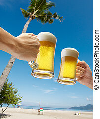 vacation - two hands holding beers toasting on beach