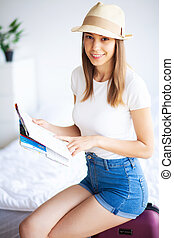 Vacation. Woman Who is Preparing for Rest. Young Beautiful Girl Sits on the Bed. Portrait of a Smiling Woman. Happy Girl Goes On Vacation