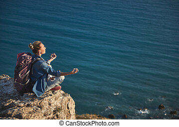 Vacationer practicing yoga on hill - Tranquil female person...