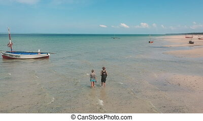 Vacationing Couple Walking in Shallow Sea Water on Beach