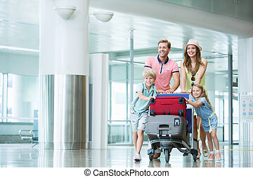 Vacations - Smiling family with children at the airport