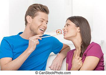 vacker, äta, sittande, par, sushi, couch, medan, annat, tillsammans., varje, nära