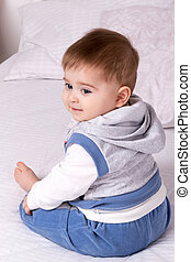 vacker baby, sängkläder, sittande