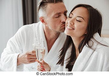 vacker, bemanna kvinna, rum, ögon, glasögon, avbild, hotell, säng, medan, närbild, asiat, stängd, kyssande, kind, drickande, champagne, caucasian, stilig
