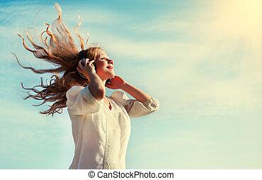 vacker, flicka, avlyssna musik, på, hörlurar, in, den, sky