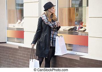 vacker, flicka, med, shopper, tittande vid, windoew, butik