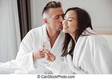 vacker, kind, stilig, kvinna, rum, avbild, hotell, säng, medan, asiat bemanna, kyssande, drickande, champagne, caucasian, glasögon
