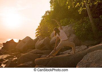 vacker, krigare, kvinna, yoga framställ, utföre, solnedgång, under, silhuett, strand