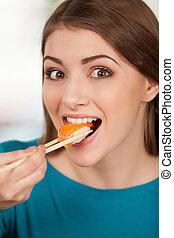 vacker kvinna, äta, sittande, min, favorite., ung, medan, le, sushi nigiri, restaurang