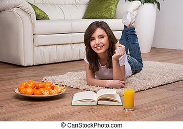 vacker kvinna, avkopplande, golv, ung, bok, hem, läsning, home., lögnaktig
