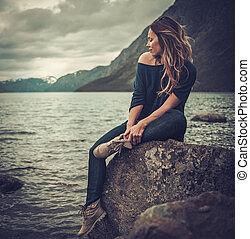 vacker kvinna, framställ, på, den, kust, av, a, vild, insjö, med, mountains, på, den, bakgrund.