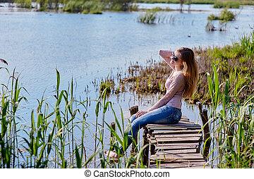 vacker kvinna, sittande, på, a, pir, hos, den, insjö
