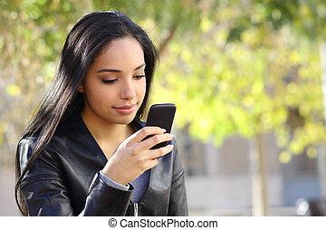 vacker kvinna, texting, på, a, smart, ringa, in, a, parkera
