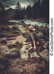 vacker kvinna, vandrare, hoppning, på, den, stenar, nära, vild, fjäll, river.