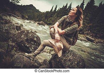 vacker kvinna, vandrare, sittande, på, den, sten, nära, vild, fjäll, river.