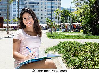 vacker, kvinnligt studerande, brasiliansk, inlärning, utomhus