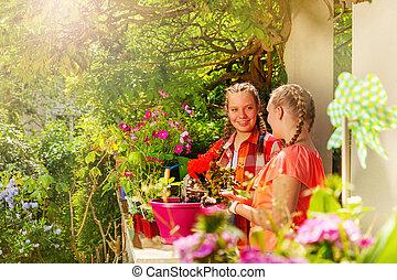 vacker, plantande, flickor, krukor, två, geranium