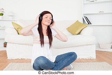 vacker, rödhårigt, kvinnlig, avlyssna musik, med, hörlurar, medan, sittande, en matta, in, den, vardagsrum