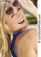 vacker, skratta, blond, kvinna, in, hjärta gestaltade solglasögoner