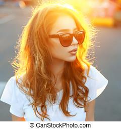 vacker, stående, av, a, nätt, solglasögoner kvinna, hos, sunset.