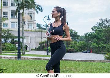 vacker, stående, fyllda, skott, holdingen, stad, lyssnande, flaska, parkera, längd, svart, hörlurar, kvinnlig, fitness, musik, modell, gräs, sportkläder
