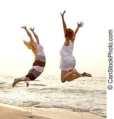 vacker, två, flickvänner, ung, hoppning, strand