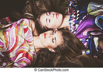 vacker, två, unga kvinnor, med, länge, blont hår, skönhet, mode, stående, lägga sig ner