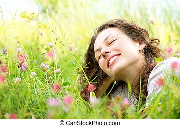 vacker, ung kvinna, lögnaktig, in, äng, av, flowers., tycka...