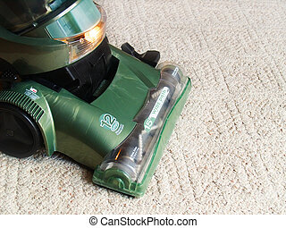 a green vacuum cleaner sweeping the carpet