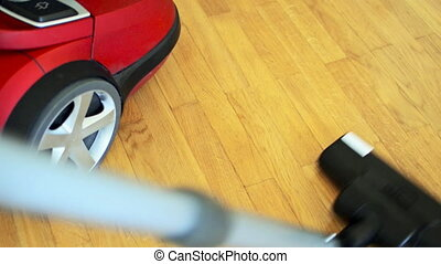 Vacuum cleaner on wooden floor.