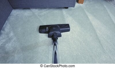 Vacuum cleaning the carpet - Vacuuming the carpet of a room